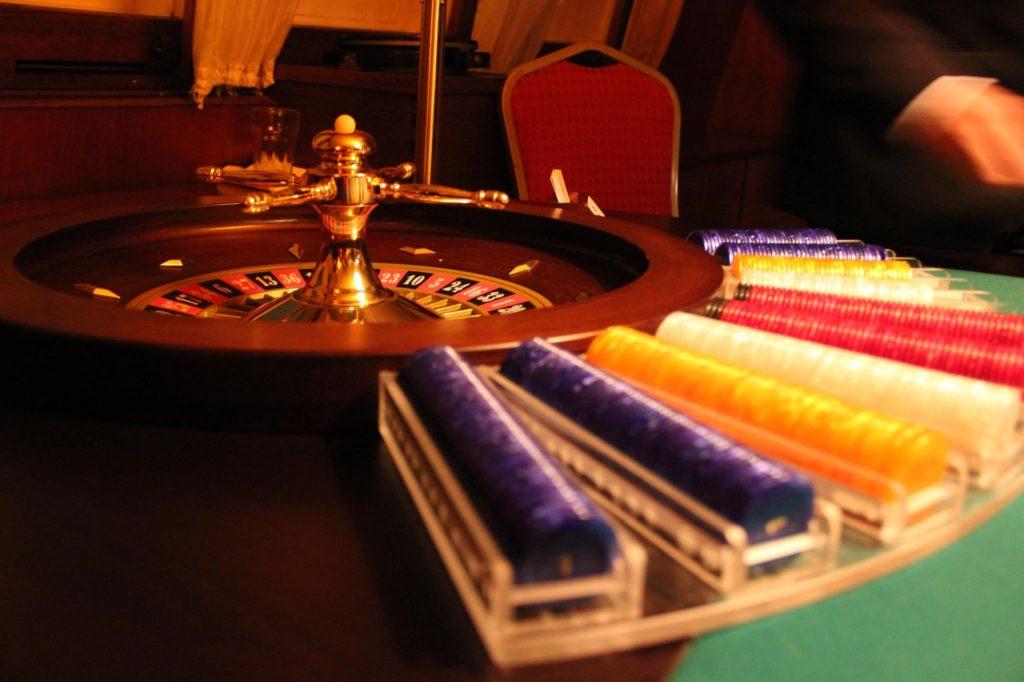 Stapel mit Chips vor einem Roulettekessel.